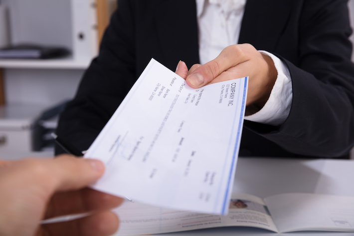 Close-up Of A Business Woman Handing Over Cheque To Her Colleague At Workplace
