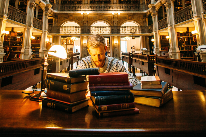 man taking notes in a well-lit library, books stacked in front of him